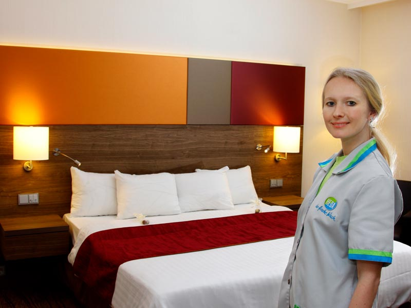 Hotelreinigung - Reinigungskraft mit sauberem Hotelzimmer